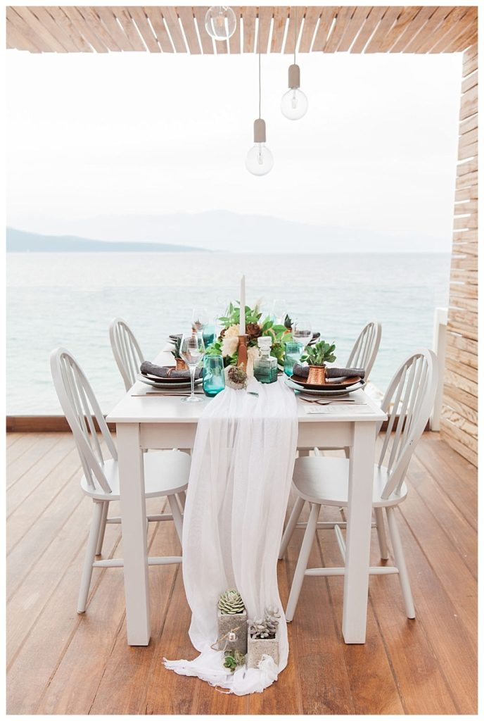 table on wooden balcony with sea view decorated in emerald and copper tones