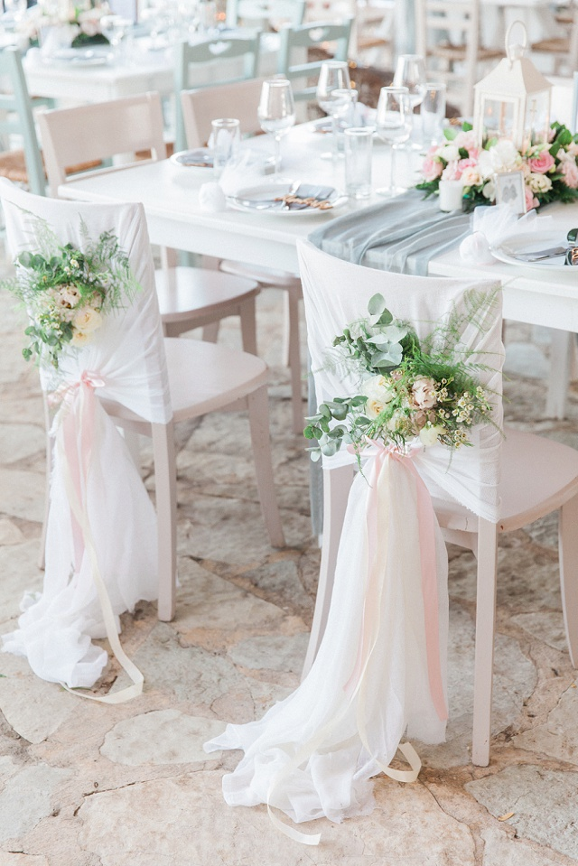 White Chairs Decorated With Greenery by Lefkas Weddings