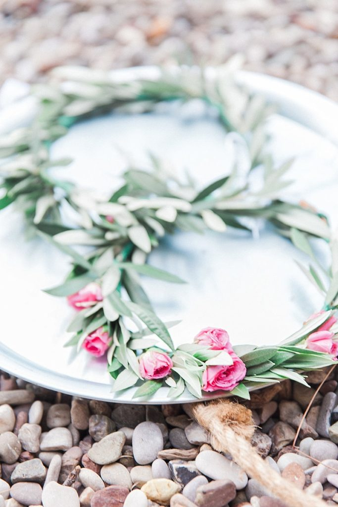 Close up image of olive and pink rose Greek wedding crowns known as Stefana on the beach