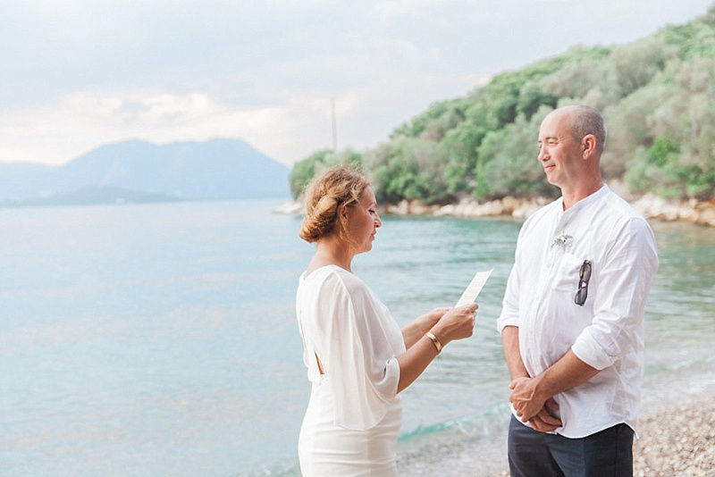 Bride reading vows to Groom standing by the sea at beach ceremony on Meganisi island
