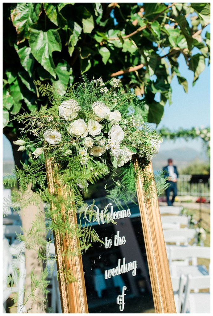 Gold cheval mirror wedding welcome sign with white and green flower decoration