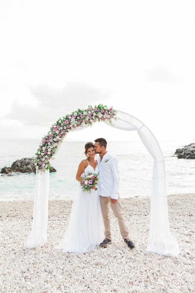 Couple Under A Floral Arch at their Secret Beach Elopement on Lefkada