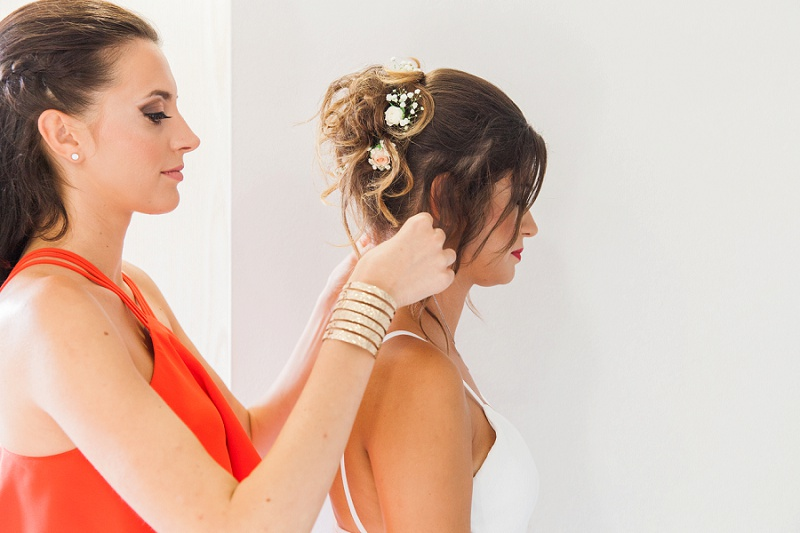 Bridesmaid Helping the Bride into Her Dress
