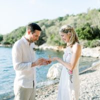 Groom placing ring on Bride's finger standing on beach at eloplement on Meganisi