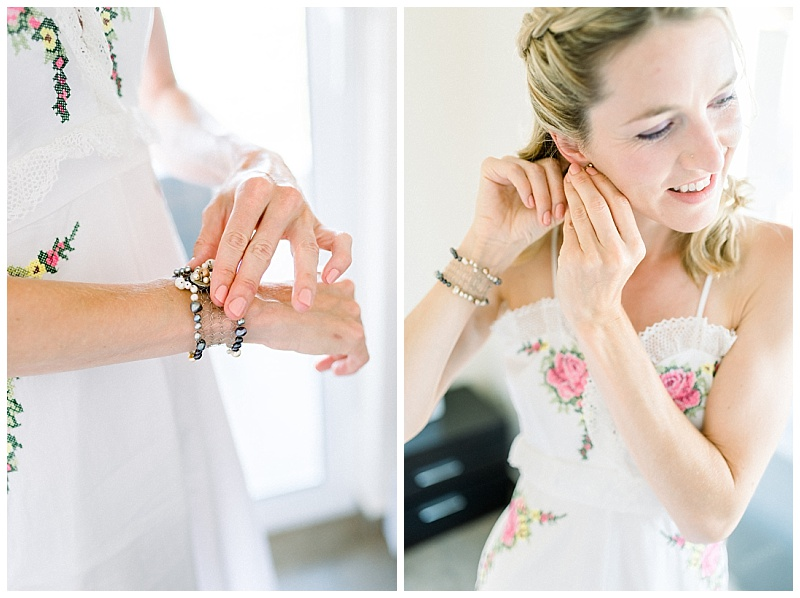 Bride in white jumpsuit putting on bracelet and earrings at villa in Meganisi