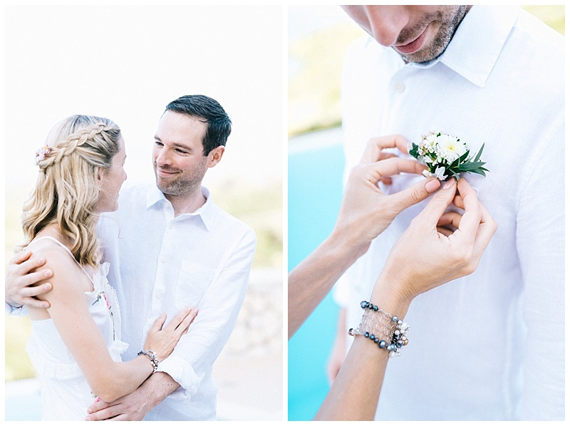 Bride pinning white buttonhole to Groom shirt at elopement in Meganisi