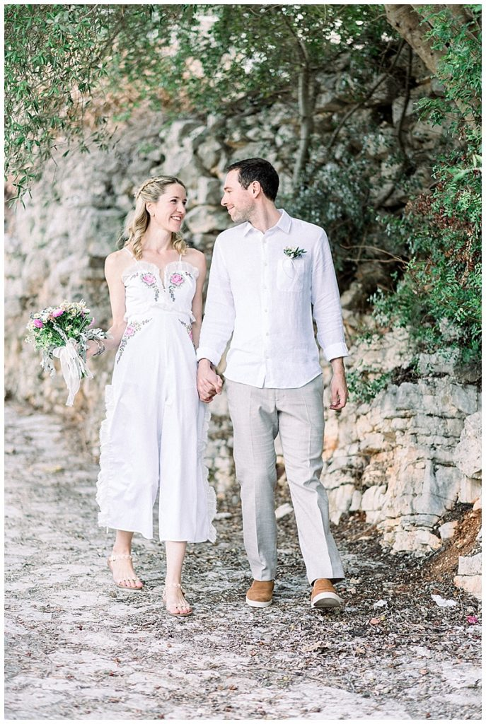 Bride and Groom walking hand in hand on path lined with olive trees and stone wall