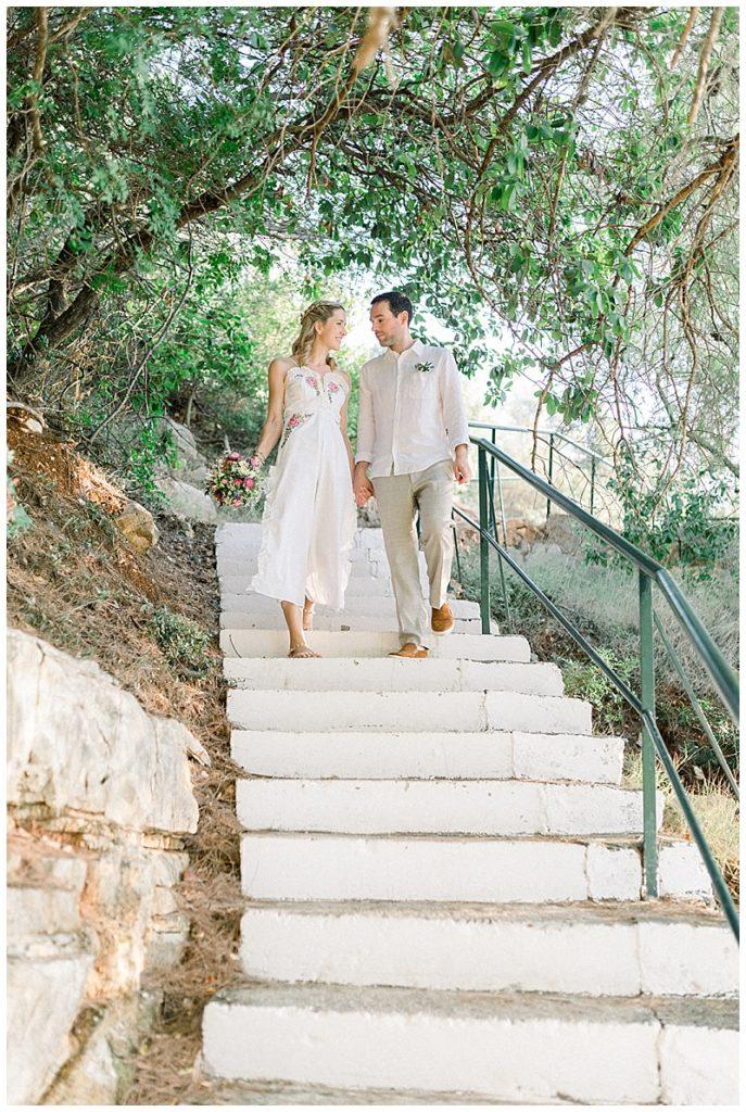 Bride and Groom hand in hand descending steps to beach elopement ceremony
