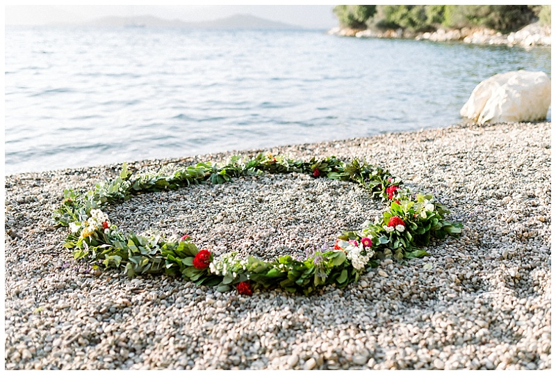 Greenery and bright flower circle wreath garland on the beach by the sea in Meganisi