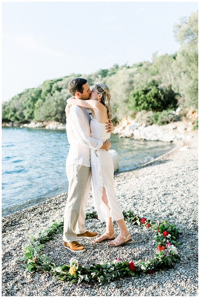 Bride and Groom embracing inside beach elopement flower circle in Meganisi