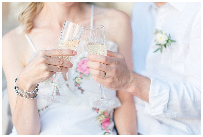 Bride and Groom toasting with champagne glasses at elopement in Meganisi