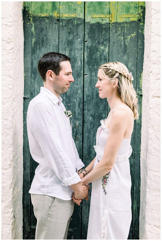 Bride and Groom standing in front of green Greek village door in Meganisi