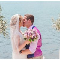 Bride and Groom kissing in middle of olive urns at ceremony by the sea