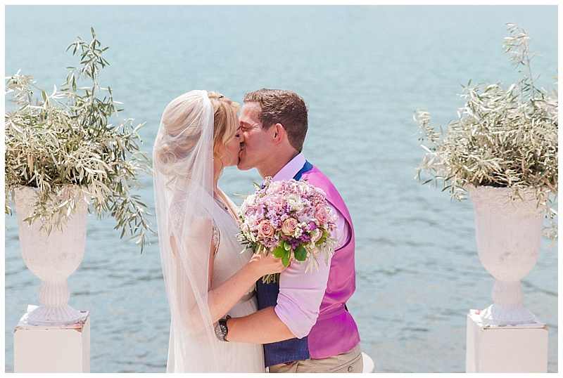 Bride and Groom kissing at ceremony by the sea