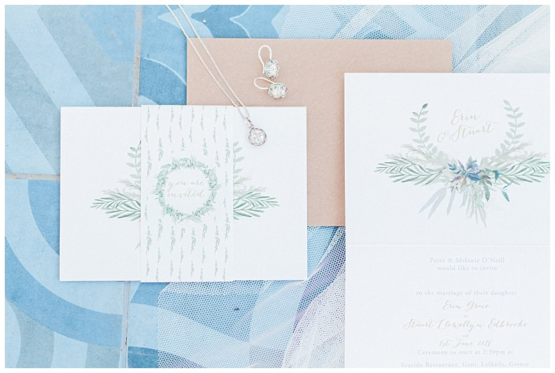 Flat lay of olive wedding stationery with jewellwey on tiled floor