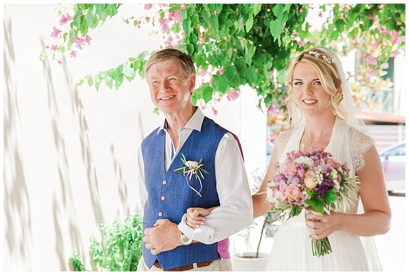 Bride arm in arm with her father walking to ceremony carrying bouquet