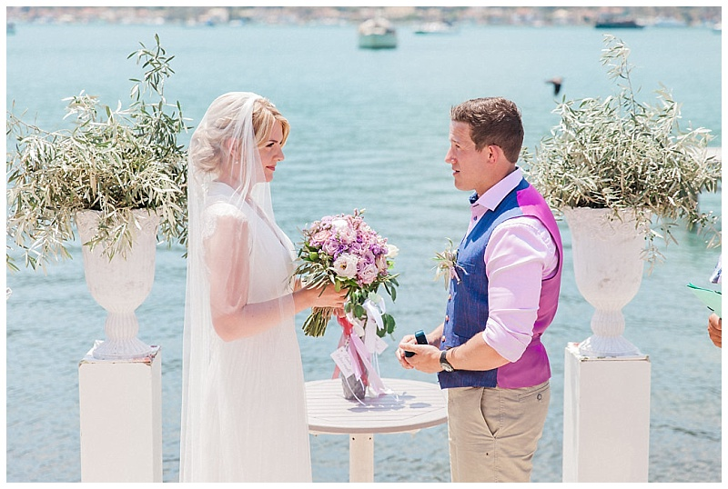 Bride and Groom facinng each other between two columns with olive at wedding ceremony on terrace by the sea