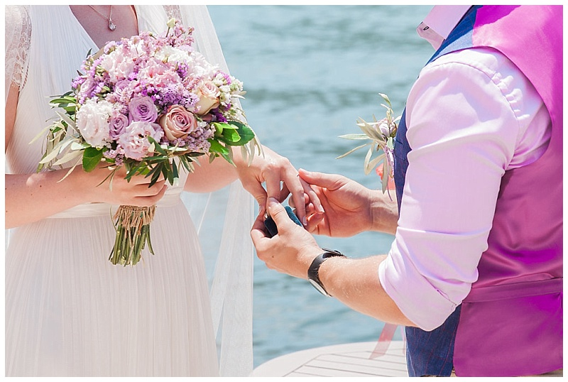 Close up of ring exchange with bride holding pink spring wedding bouquet