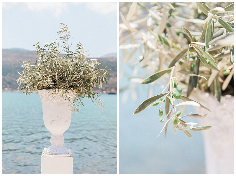 white urns filled with olive branches sat on columns as wedding ceremony decoration