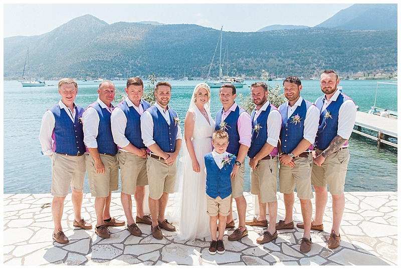 Bride and groom with groomsmen in blue waistcoats pink shirts and beige shorts