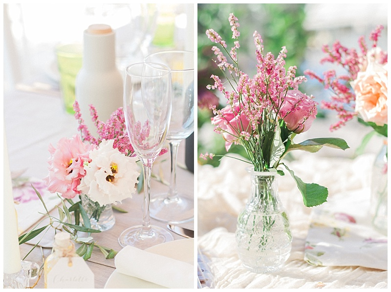 Cut glasses vases with pink spring flowers and olive on wedding dinner table