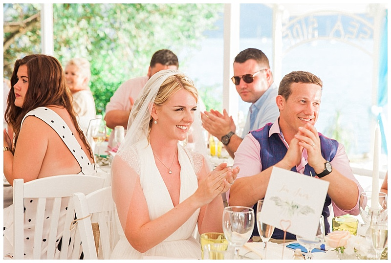 Bride and Groom sat at dinner table clapping speeches and smiling