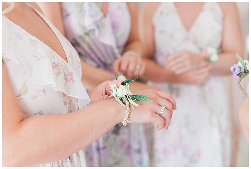 Bridesmaids putting flower corsages on to their wrists
