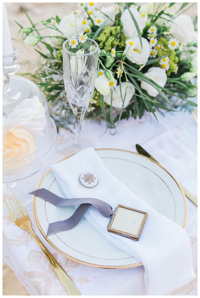 Beach elopement tablescape with white and gold flatware