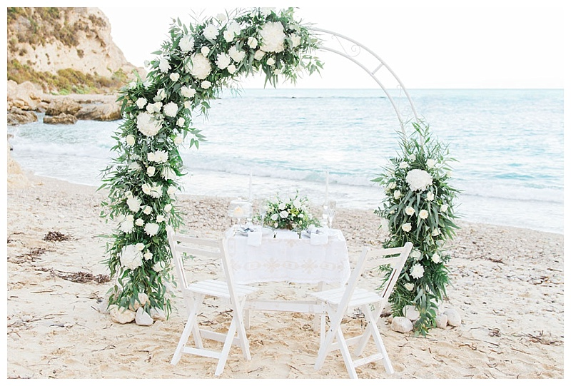 Beach wedding arch and table on the sand decorated with white and green flowers