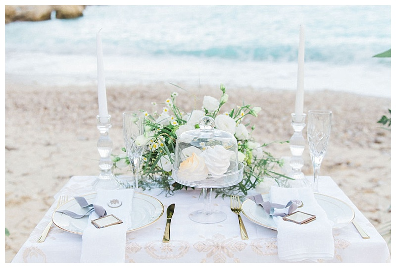 Landscape image of beach elopement tablescape in white and gold set for two people