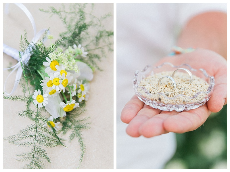 white and yellow daisy buttonhole and groom holding crystal dish with sand and wedding rings inside