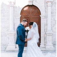 Bride and groom facing each other in front of church door in Lefkada town