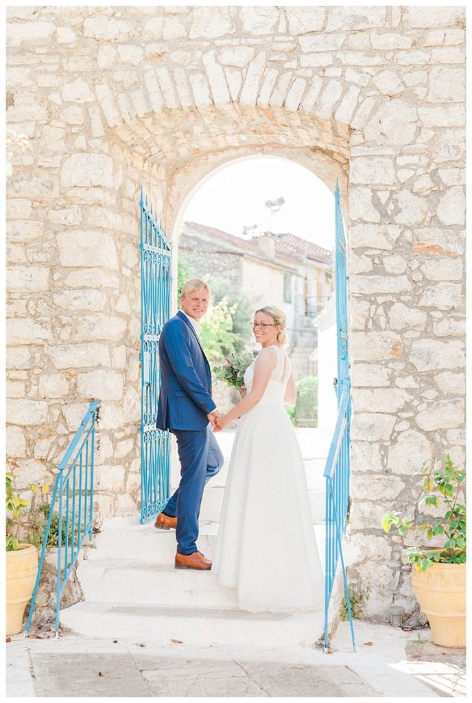 Groom and bride on steps entering greek stone church with blue railings