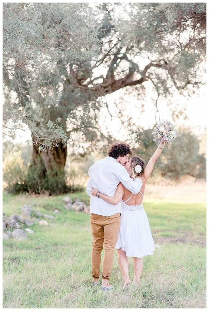 couple embracing in front of olive tree