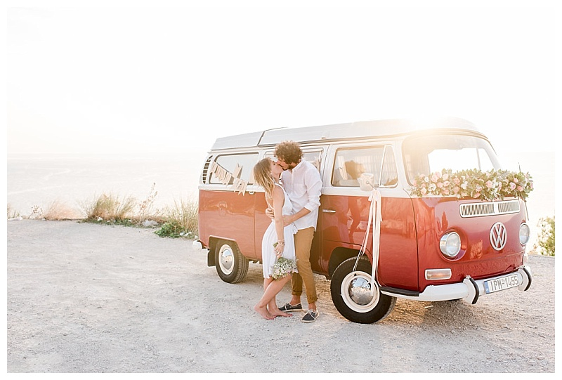 couple standing by side of vw camper at sunset on greek island