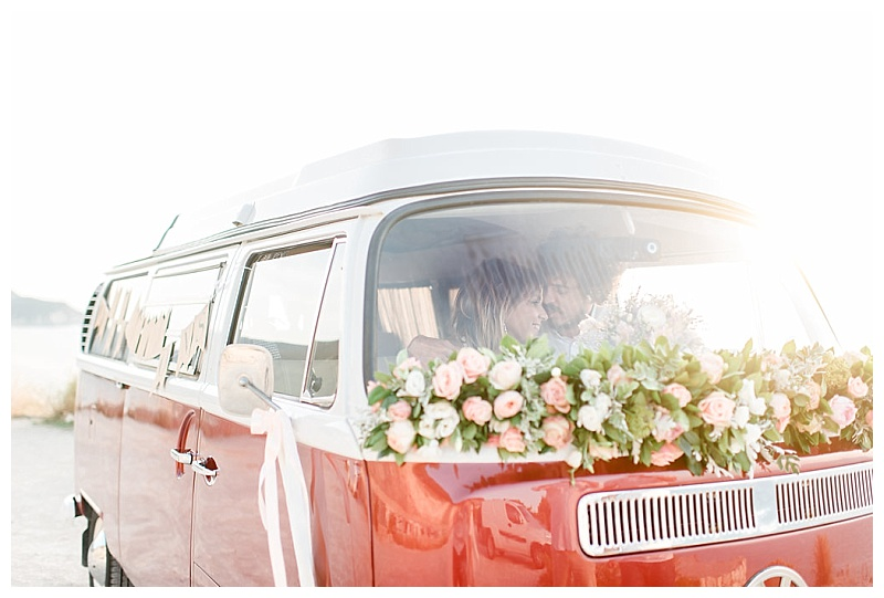 couple sat inside vw camper van with wedding flower decoration