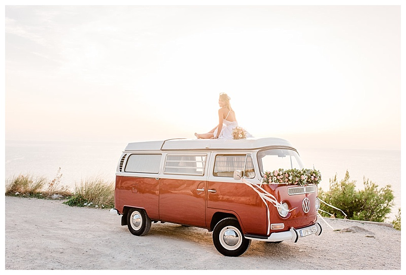 girl sitting on roof of wedding flower decorated intage red vw camper van at sunset