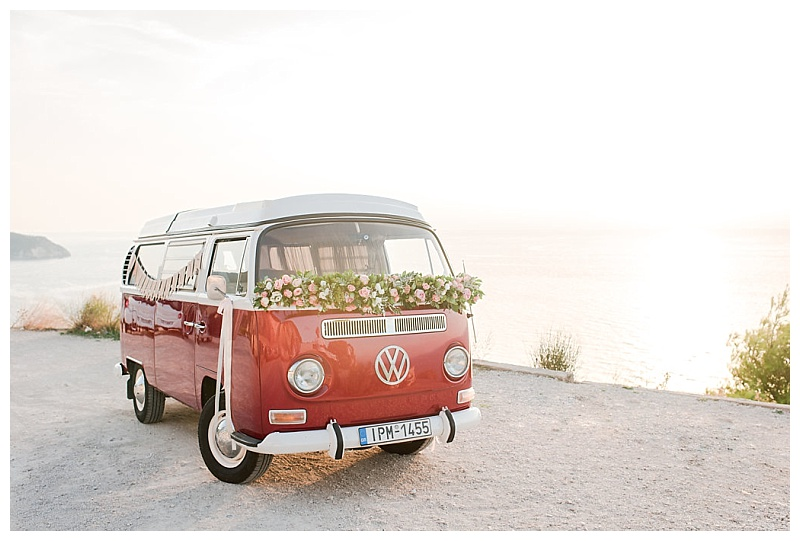 vintage red vw camper van with flowers on coast road lefkada