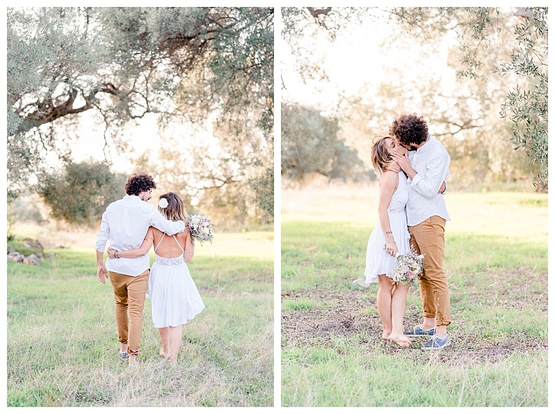 couple walking away with arms around each other in olive grove