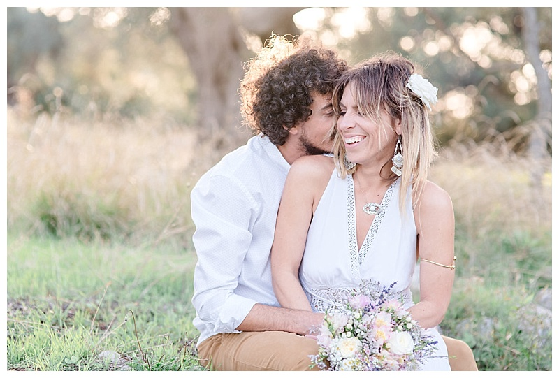 couple sitting together in olive grove with floral bouquet