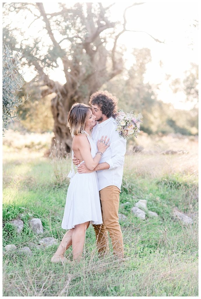 couple with arms around each other in front of a large old olive tree