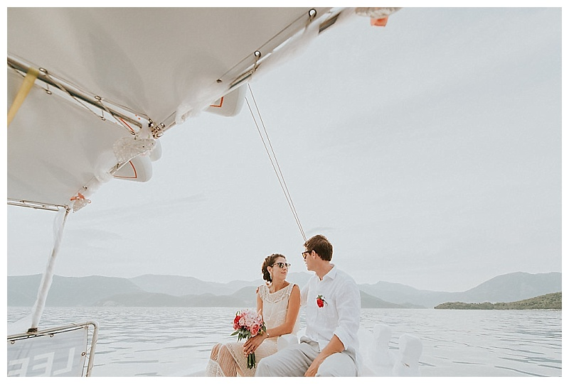 Elopement couple sat at front of boat looking at each other