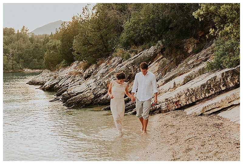 elopement couple hand in hand walking along beach at skorpios island