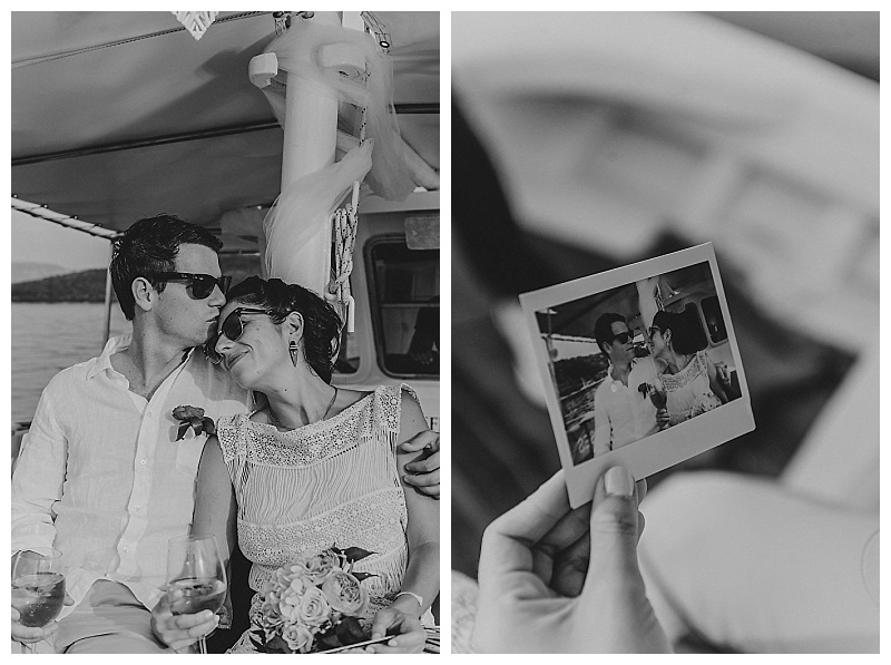 black and white image of couple on boat holding a polaroid of themselves