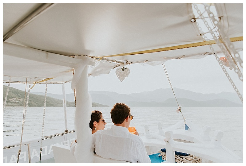 elopement couple sat at front of boat on wedding cruise looking out to sea