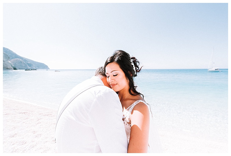 bride and groom with head on each others shoulders at porto katsiki beach lefkada