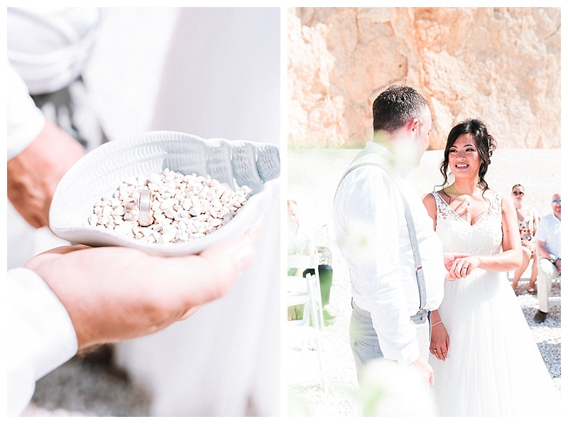 Close up of groom holding shell filled with sand and wedding rings