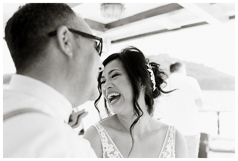 black and white image of bride and groom laughing faces