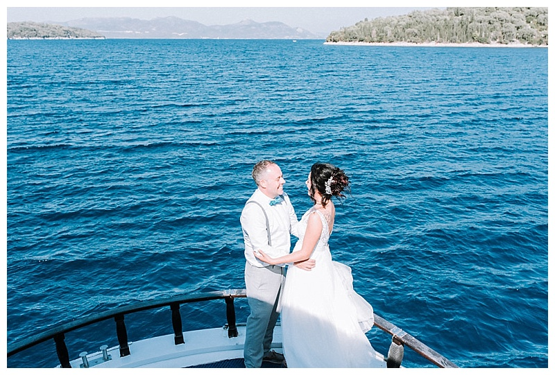 bride and groom standing at front of Lefkada cruise boat