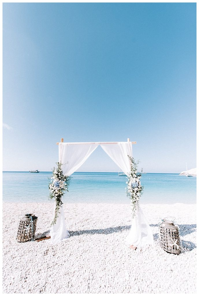 wedding arch with blue and white flowers on the sand at porto katsiki beach lefkada